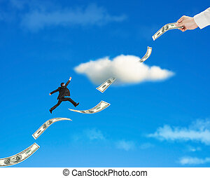 Businessman jumping on money trend through cloud with hand...