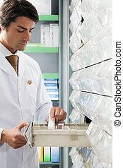 pharmacy - pharmacist taking medicine from drawer. Copy...