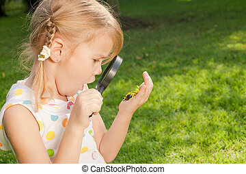 one little girl with magnifying glass outdoors in the day...