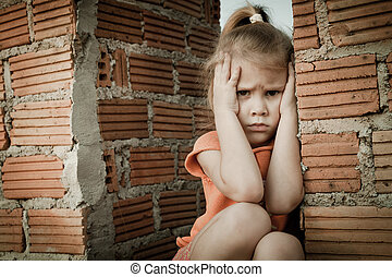 Portrait of sad little girl sitting near brick wall in the...