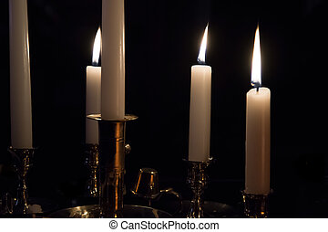 Varios Lit White Candles in Brass Candlestick Holders