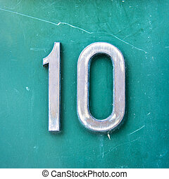 Number 10 - metal house number ten on a green background.