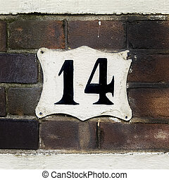 Number 14 - house number fourteen on a brick wall.