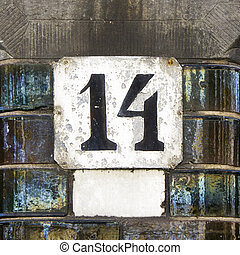 Number 14 - Weathered house number fourteen. Black lettering...