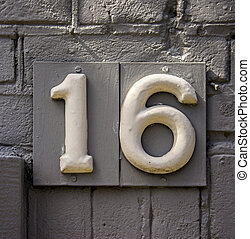 Number 16 - House number sixteen on a painted brick wall.