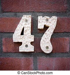 Number 47 - ceramic house number forty seven on a brick wall...
