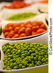 Peas and Tomatoes - Vegetables at a Salad bar of fresh green...