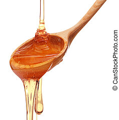 Honey dripping from a wooden honey dipper isolated on white...