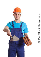 Putty knife and brick - A builder holding a putty knife and...