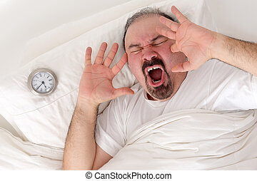 Man yawning loudly resting in bed - Middle-aged bearded man...