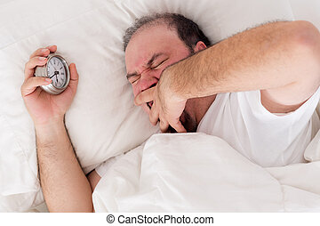Man yawning as he tries to wake up - Man lying in bed...
