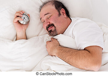 Man smiling in contentment after a good sleep - Man lying in...