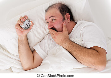 Man suffering from insomnia trying to sleep checking the...
