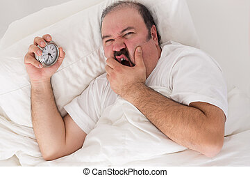 Man suffering from insomnia lying in bed clutching his alarm...