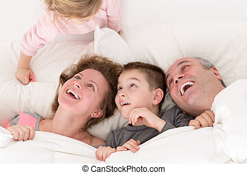 Playful little girl with her family in bed