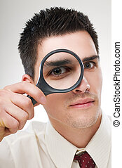 loupe - young business man looking through loupe close up