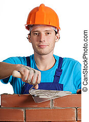 Bricklayer with putty knife - A bricklayer in orange helmet...