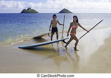 Japanese couple on paddle boards - Japanese couple on stand...