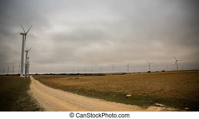 Wind turbines - Modern Wind turbines and track on a cloudy...