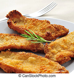 a plate with some spanish escalopa de pollo a la milanesa,...