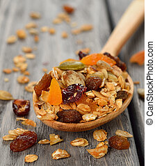 Granola with fruit and nuts on gray background