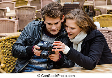 Couple Looking At Photographs On Camera At Restaurant
