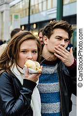 Woman Eating Hotdog While Man Cleaning Mouth