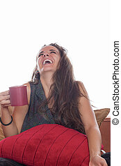 smiling woman with coffee on sofa