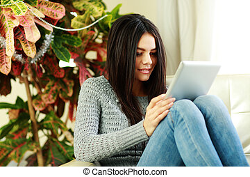 Young beautiful woman sitting on the armchair with tablet computer at home