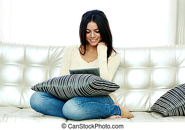 Portrait of a happy woman sitting on the sofa and using...