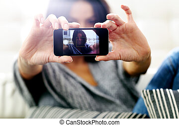 Young happy woman making self photo with her smartphone....