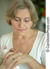 Senior woman applying cream on hands