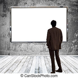 Man in gallery room looking at huge empty billboard