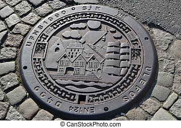 sewer manhole - A cast-iron sewer manhole on the stone-paved...
