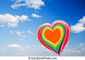 Colorful heart shaped lollipop on sky background