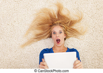 Shocked blonde woman with digital tablet