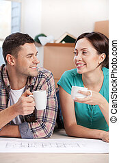 Planning a house improvement. Cheerful young couple lying on the floor and drinking coffee while cardboard boxes laying on the background