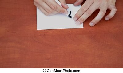 Handwritten word Now on white paper sheet