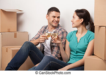 Celebrating their moving to a new apartment. Cheerful young couple sitting on the floor and drinking wine while cardboard boxes laying around them