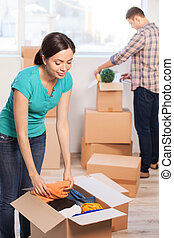 Unpacking. Beautiful young woman unpacking a carton box while man unpacking a cardboard box on the background