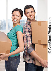 Moving to a new house. Cheerful young couple standing close to each other and smiling at camera while holding cardboard boxes