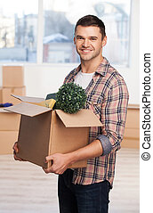 Just moved in a new house. Handsome young man holding an cardboard box with home stuff in it and smiling while more carton boxes laying on background