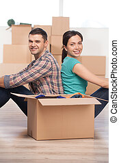 Together in a new house. Beautiful young couple sitting close to each other and smiling while cardboard boxes laying all around them