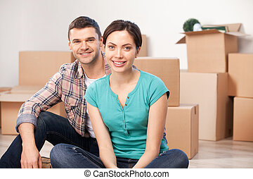 Together in a new apartment Cheerful young couple sitting...