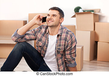 Calling from a new house. Cheerful young man sitting on the floor and talking on the mobile phone while cardboard boxes laying on the background