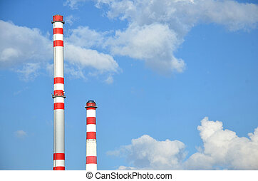 Two factory chimneys with sky in the background