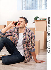Calling from a new apartment. Handsome young man sitting on the floor and talking on the mobile phone while cardboard boxes laying on the background