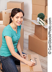Marking a carton box. Top view of cheerful young woman marking a cardboard box and looking at camera while more boxes laying on background