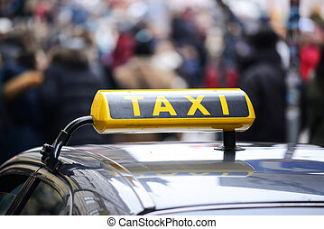 Taxi car in town centre crowded with pedestrians