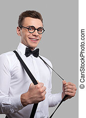 Confident nerd Cheerful young man in bow tie adjusting his...